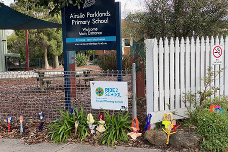 Ainslie Parklands Primary School with decorated wooden spoons at the front gate