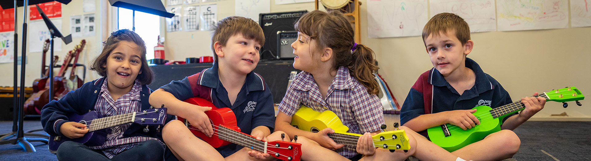 primary school students in music class playing ukuleles