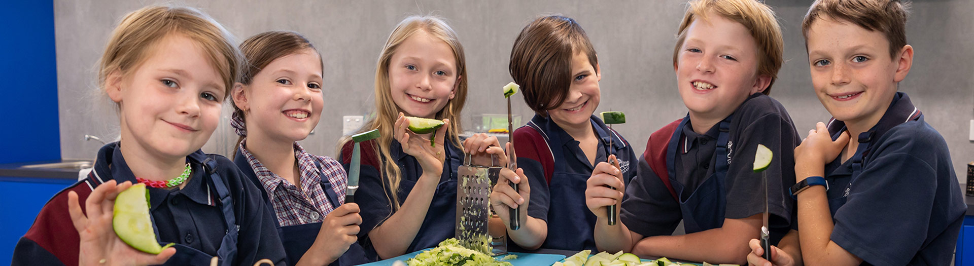 smiling students grating zucchini in a school kitchen